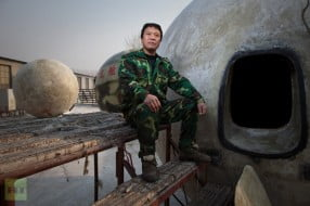 Liu Qiyuan posing with survival pods
