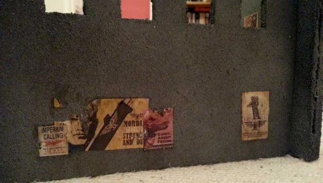 Multiple propaganda posters beneath a balcony of windows