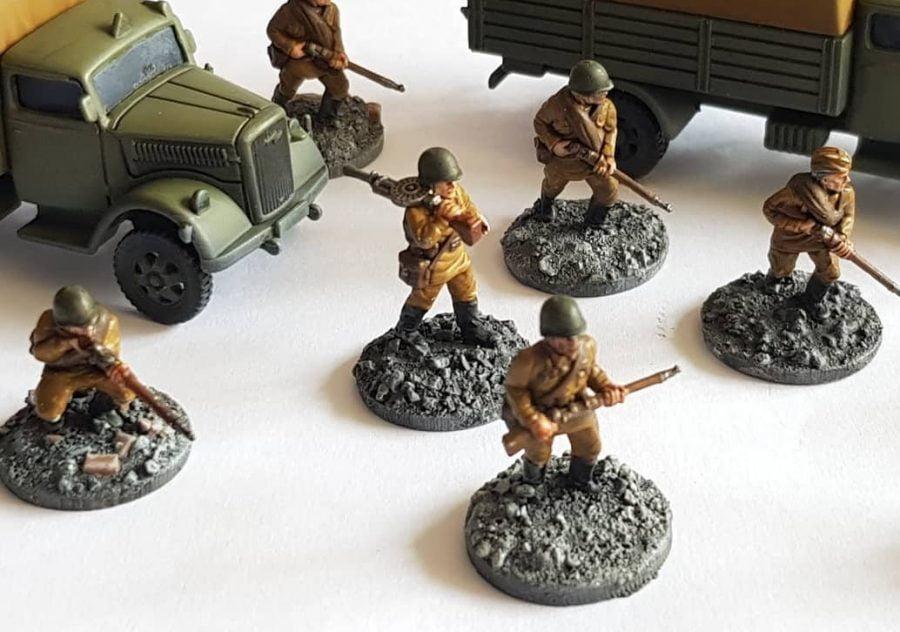 Soviet riflemen patrol alongside 2x WW2 trucks